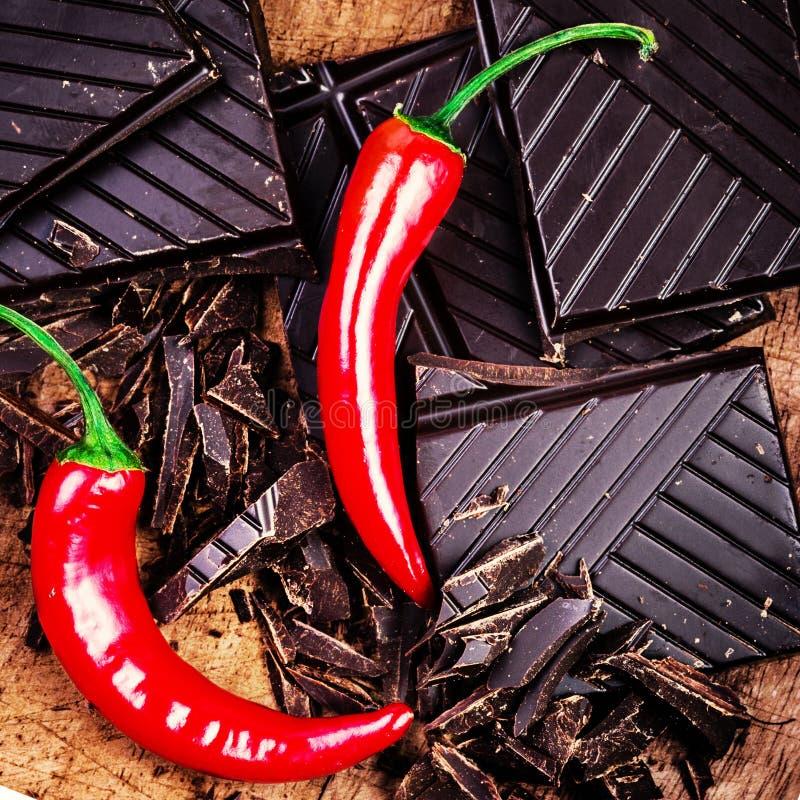 Перец красного Chili с прерванным шоколадным батончиком на деревянной предпосылке стоковые фото