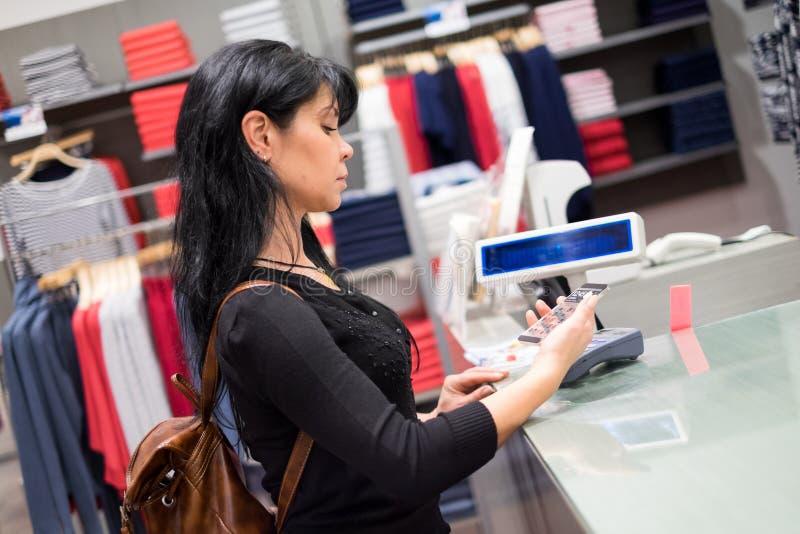 передвижная компенсация Девушка оплачивает ходить по магазинам используя мобильный телефон стоковое изображение