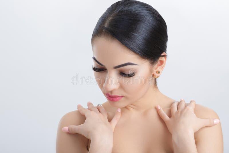 Передний портрет привлекательной молодой женщины брюнет на сером крупном плане предпосылки очистьте кожу девушки стоковая фотография
