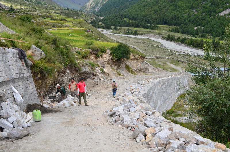 Передовица: 22-ое августа 2011: Chitkul, Sangla, Himachal, Индия: Неопознанные работники делая дорогу и туриста идут для прогулки стоковое фото rf