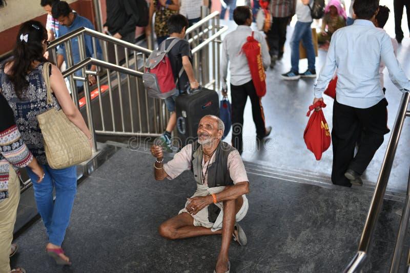 Передовица: Gurgaon, Дели, Индия: 6-ое июня 2015: Неопознанный старый бедный человек умоляя от людей на Gurgaon, Дели m Метро дор стоковые фотографии rf