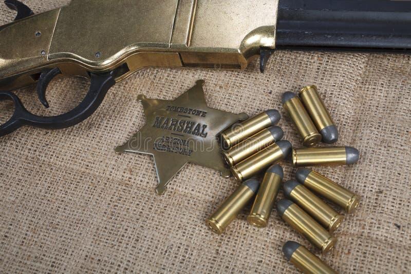 Период Диких Западов повторяя винтовку с значком боеприпасов и шерифа стоковые изображения rf