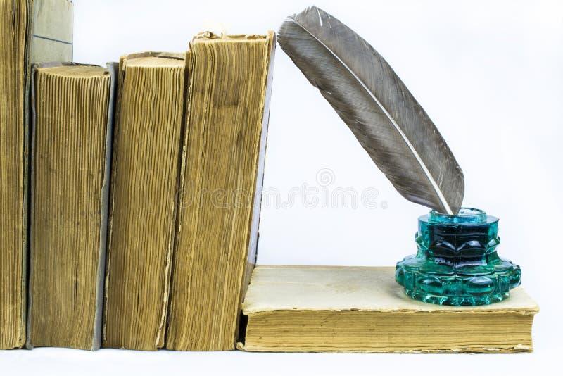 Перо в зеленой чернильнице, старых книгах изолированных на белой предпосылке стоковое изображение rf