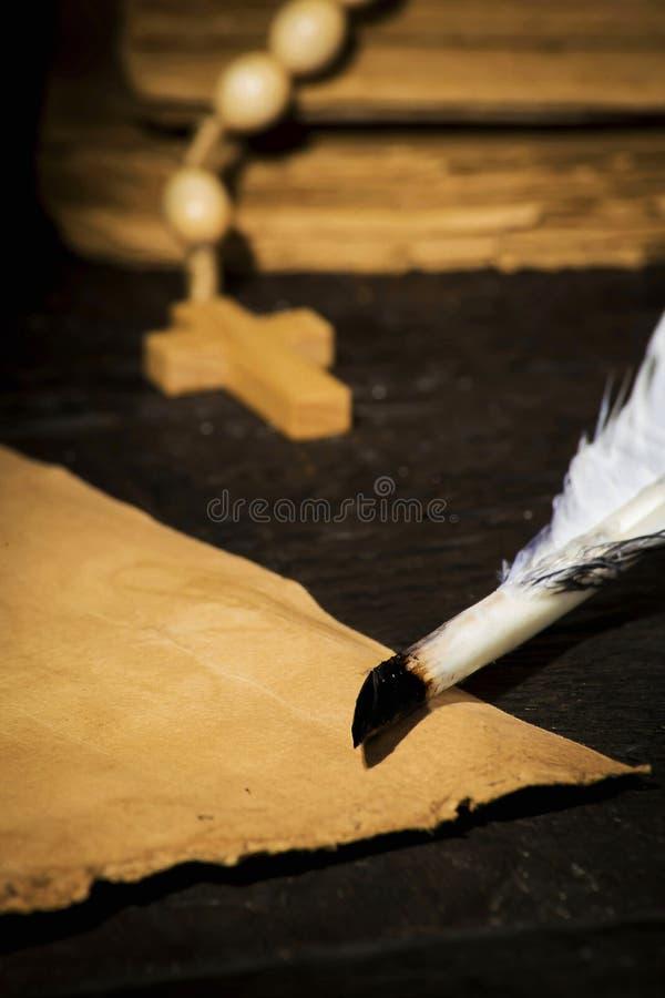 Перо птицы со старым пергаментом на предпосылке книг стоковая фотография