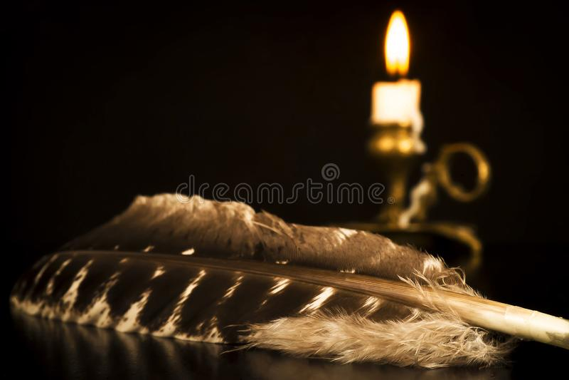 Перо птицы с подсвечником и освещенной свечой на заднем плане стоковое фото rf