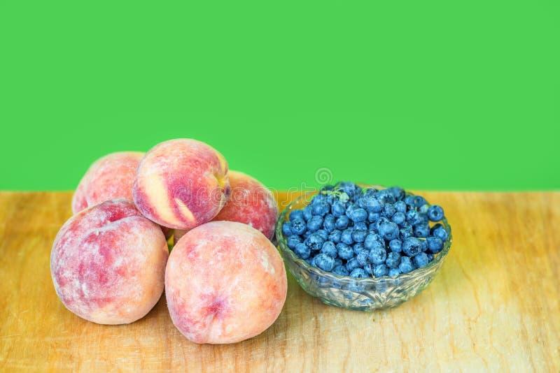 Персики на деревянной доске и свежих голубиках в стеклянной вазе стоковые фотографии rf