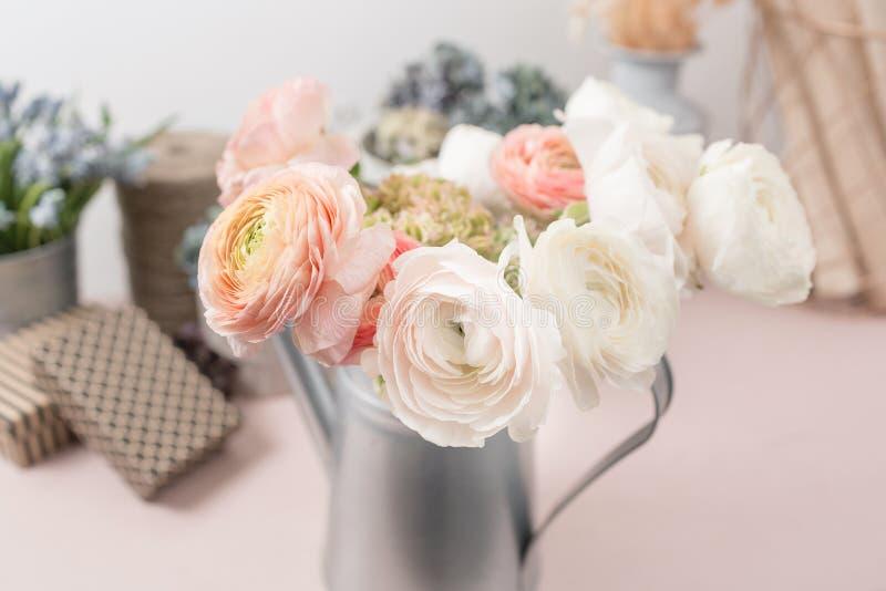 Перский лютик Лютик пука красочный цветет светлая предпосылка Ваза металла на розовом винтажном деревянном столе стоковая фотография rf