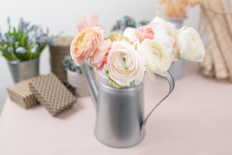 Перский лютик Лютик пука красочный цветет светлая предпосылка Ваза металла на розовом винтажном деревянном столе стоковое изображение rf