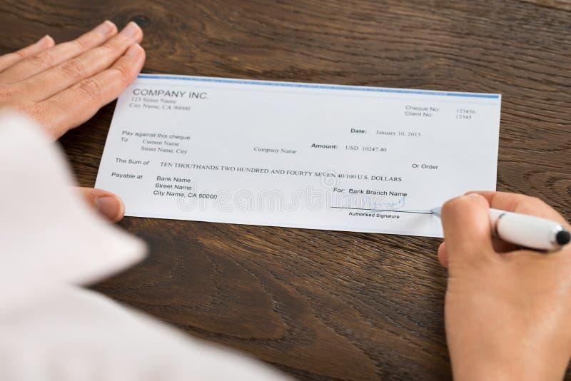 Персона вручает чек подписания с ручкой стоковые изображения