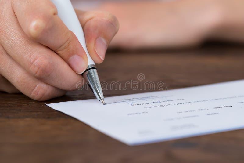 Персона вручает чек подписания стоковое фото rf