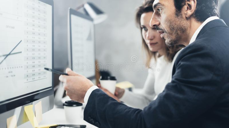 Персона 2 дел на работая процессе на офисе Молодые профессионалы работают с проектом нового рынка на настольных компьютерах стоковые фото
