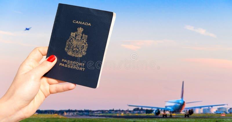 Персона держа канадский пасспорт при один самолет ездя на такси и другие принимая  стоковая фотография