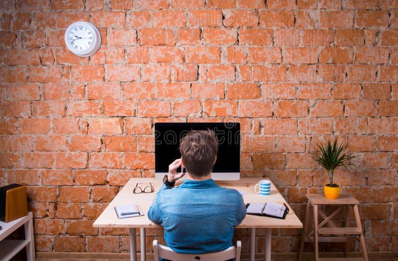 Персона дела сидя на столе офиса, говоря на телефоне стоковые фотографии rf