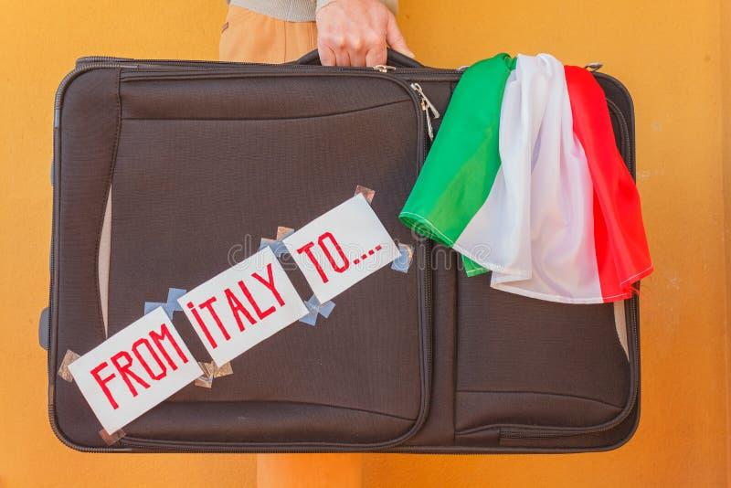 Персона имеет чемодан в руке, который нужно эмигрировать от Италии стоковая фотография rf