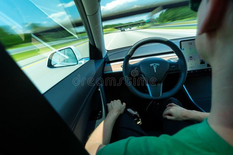 Персона используя само-управляя функцию в полностью электрической модели 3 Tesla стоковое изображение rf