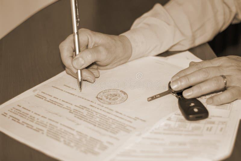 Персона подписывая документ на продаже машины стоковые изображения