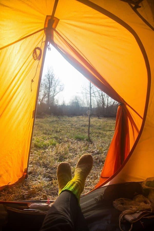 Персона сидя в оранжевом шатре, лагерь в банке реки весной Ноги selfie путешественника Расслабленный, красочный взгляд стоковая фотография