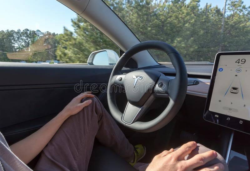Персона управляя новой моделью 3 Tesla в режиме автопилота стоковое фото rf