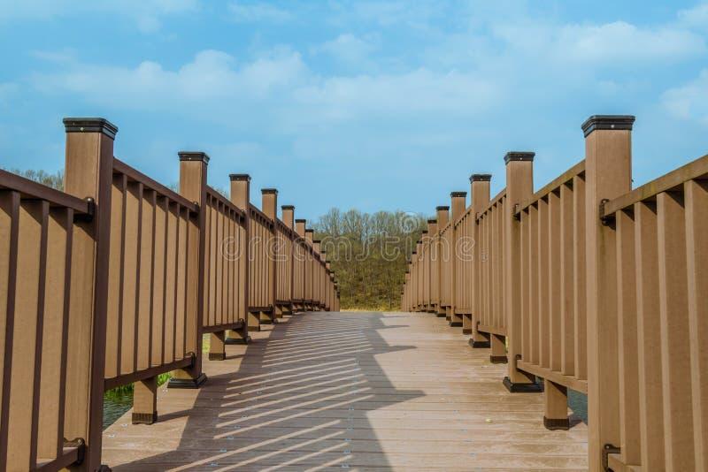 Перспектива крупного плана деревянного footbridge с деревьями и отчасти c стоковые фотографии rf
