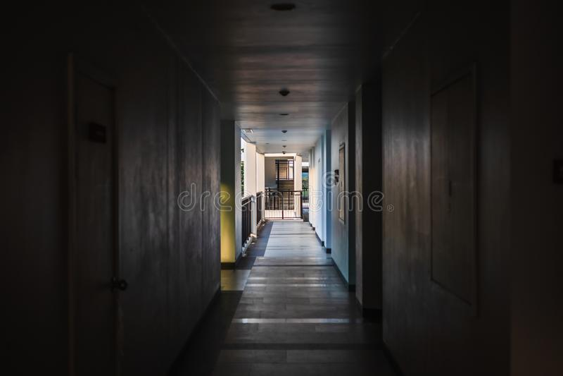 Перспектива пустого коридора в жилом доме с дверями и и пожарной лестницей и светом в конце пути стоковые фотографии rf