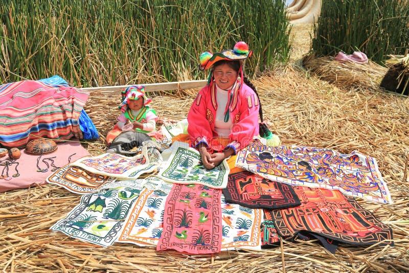 Перуанская женщина на острове Uros в традиционной красочной ткани стоковое фото rf