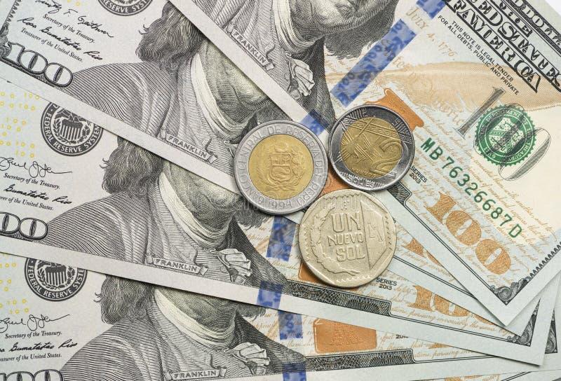 Перуанские подошвы чеканят поверх долларовых банкнот стоковая фотография rf