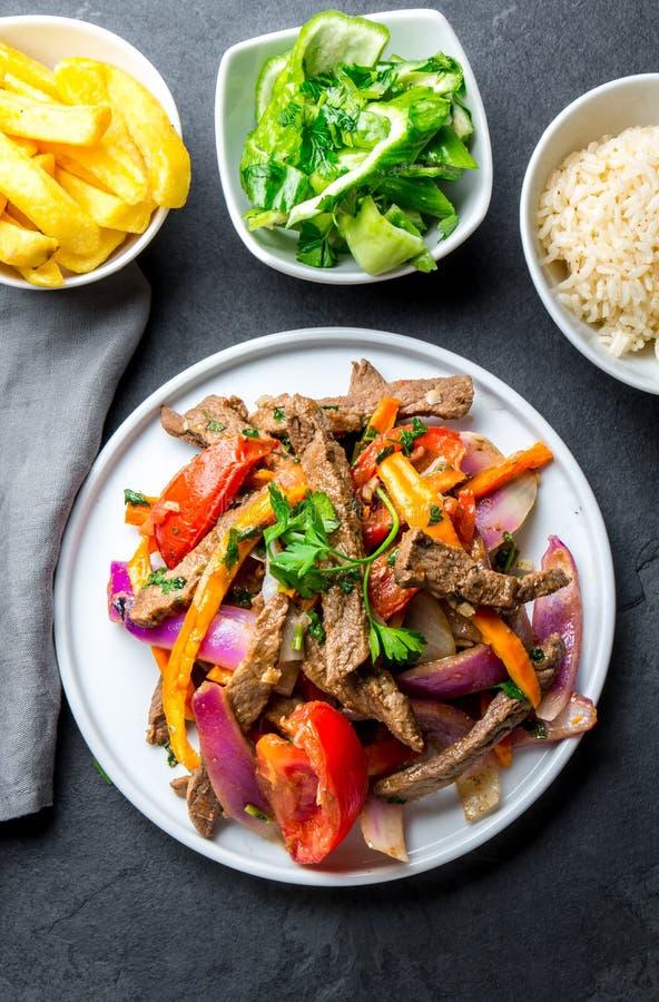Перуанское saltado Lomo блюда - tenderloin говядины с фиолетовым луком, желтым chili, томатами служил на белой плите, шифере стоковая фотография