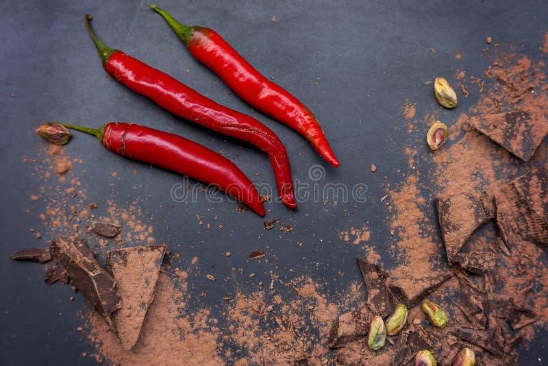 Перцы красного chili и темные части шоколада стоковое фото