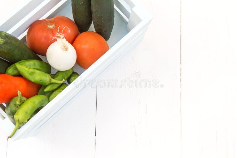Перцы, томаты, огурцы и луки заполненные в деревянную коробку стоковое изображение