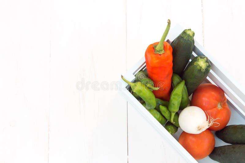 Перцы, томаты, огурцы и луки заполненные в деревянную коробку стоковое фото