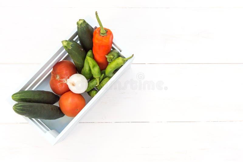 Перцы, томаты, огурцы и луки заполненные в деревянную коробку стоковое фото rf