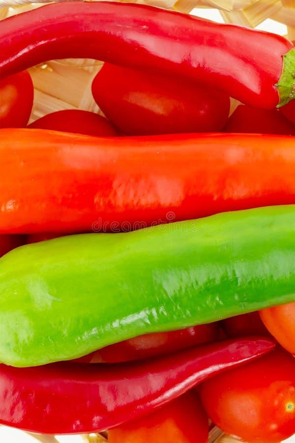 Перцы яркой параллели овоща предпосылки горизонтальные горячие на томатах вишни в деревянной предпосылке стоковые изображения