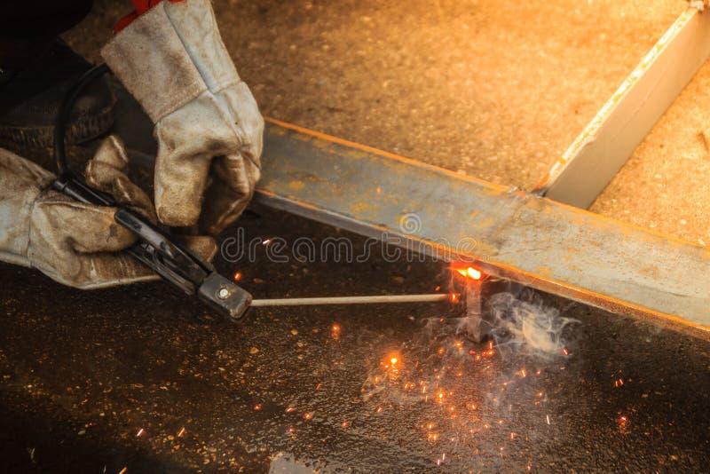 Перчатка руки носки сварщика защитная держит электрод и w стоковая фотография