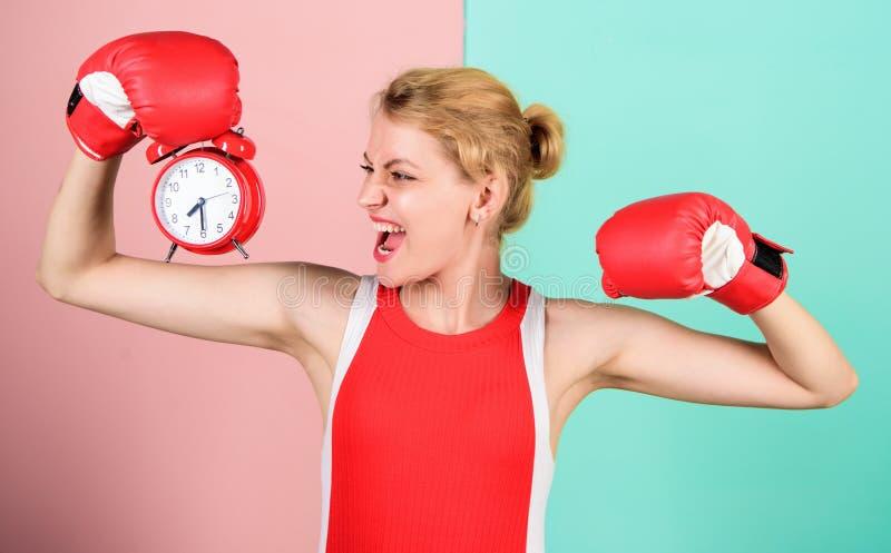 Перчатки бокса спортсмена девушки и будильник Образ жизни спорта и здоровый режим Привычки и концепция режима улучшите стоковые фото