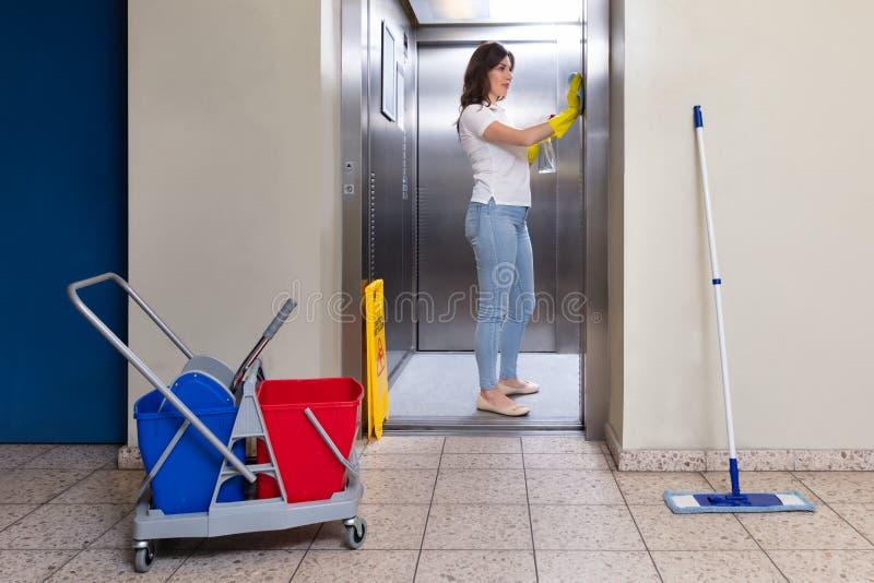 Перчатки женского привратника нося очищая лифт стоковое фото