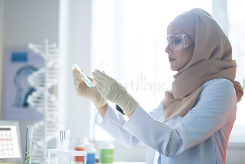 Перчатки и стекла химика нося пока держащ пробирки стоковое изображение