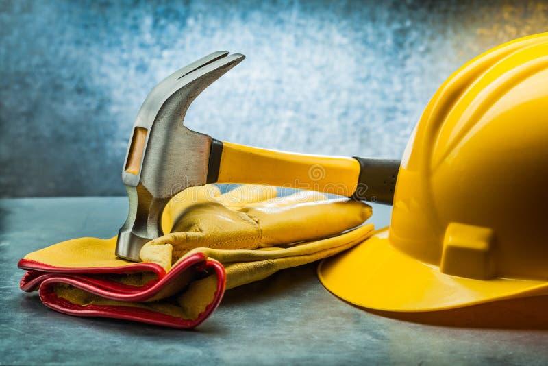 Перчатки кожи конструкции молотка с раздвоенным хвостом и желтый шлем на металлической предпосылке стоковая фотография