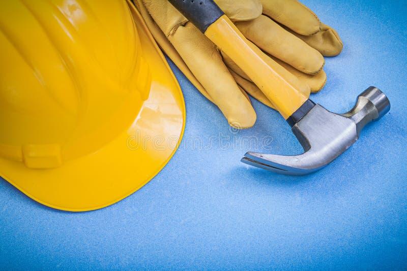 Перчатки молотка с раздвоенным хвостом кожаные защитные строя шлем на голубом ба стоковое фото rf