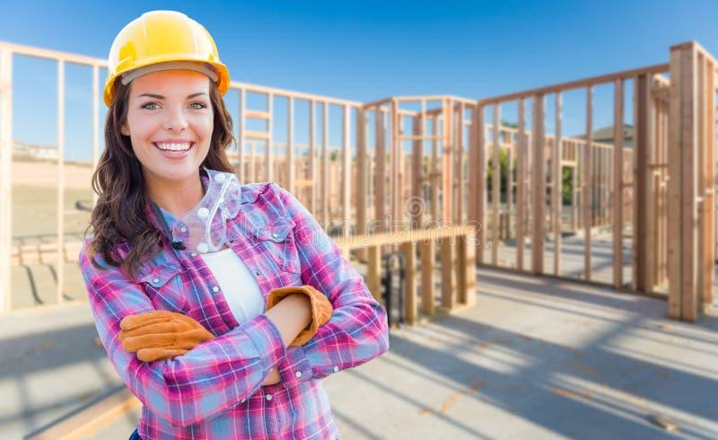 Перчатки молодого привлекательного женского рабочий-строителя нося, крепко стоковая фотография