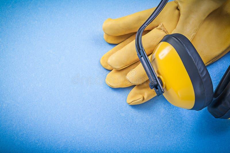 Перчатки протекторов уха защитные на голубой конструкции предпосылки стоковое фото
