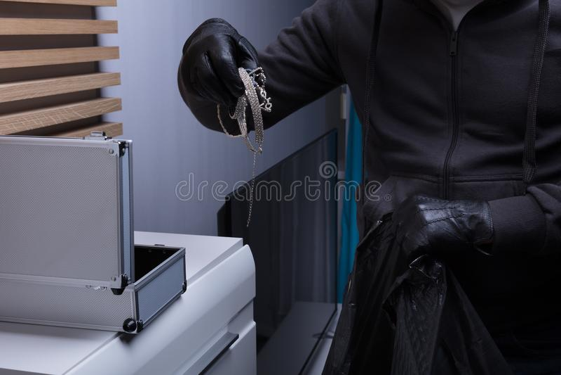 Перчатки разбойника нося крадя ювелирные изделия стоковые фото