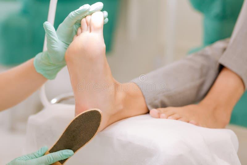 Перчатки Chiropodist нося держа скруббер ног в ее руке стоковое фото rf