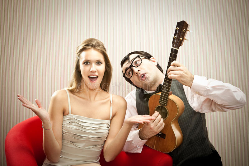 Песня о любви гавайской гитары игры парня человека болвана для его подруги на день валентинки стоковые изображения