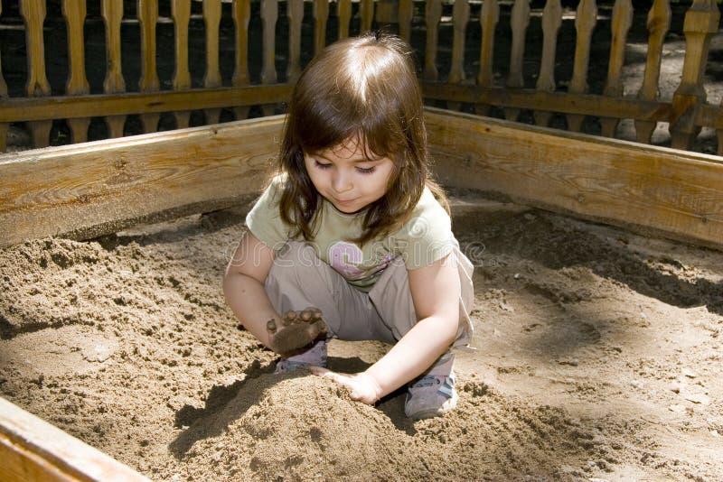 песок девушки ребенка коробки plaing стоковое фото