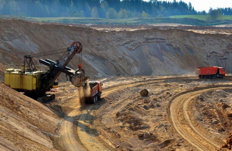 Песок загрузки экскаватора карьера или в самосвал на opencast раскопк минеральных ресурсов, работе особенного минирования стоковые фото