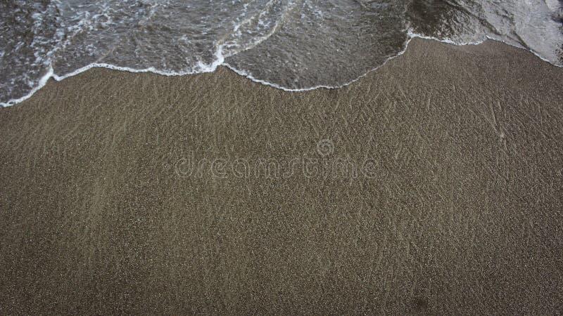 Песок и маленькие волны формируя красивую текстуру на пляже стоковое изображение rf