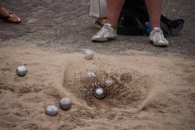 Песок летает прочь когда шарик приземлится на том основании во время игры boules стоковые изображения rf