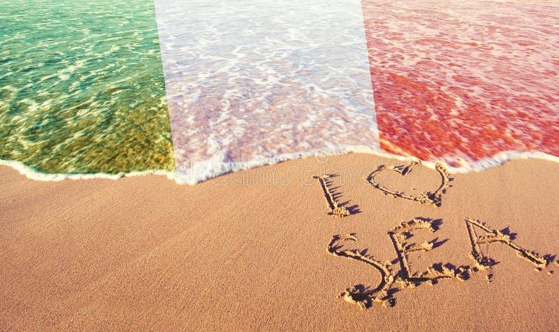Песок пляжа, море и флаг Италия Я люблю концепцию Италии стоковое фото rf