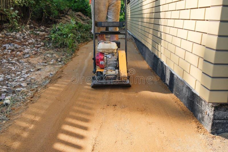 Песок построителя трамбуя вокруг дома на строительной площадке стоковые фотографии rf