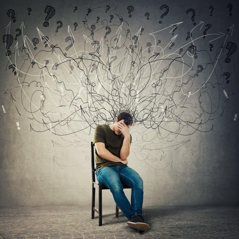 Пессимистический, разочарованный человек сидя на стуле в темной комнате, страдает тревожность, чувство депрессии дистресса стоковые фотографии rf